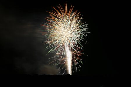 Beautiful, colorful patterns of light created in the dark, night sky as sparks from exploding fireworks scatter and fly in all directions creating beautiful, glowing flower and ball shapes for July 4th or New Years Eve festival celebrations.
