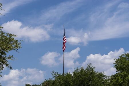 The United States Flag hanging limply on a flag pole over some trees on a a calm, cloudy day with no wind to make it wave proudly.