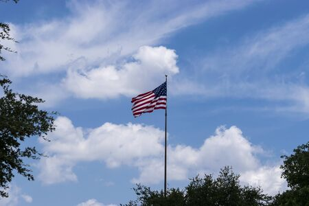 United States flag rippling in the wind as it rises above some trees with a blue sky filling with fluffy white clouds as a beautiful background. 写真素材