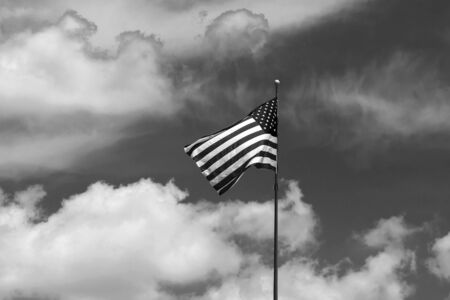 Black and white photo of the Flag of the United States of America waiving at the of a flag pole on a windy summer afternoon with blues skies partly covered by clouds in the background.