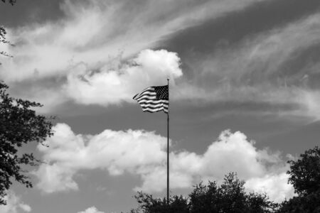 Black and white photo of the United States flag waving proudly in the wind on a flag pole rising above the trees with  partly cloudy skies in the background.