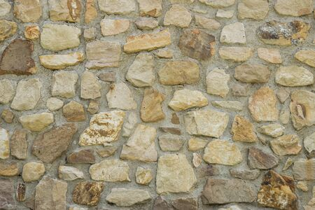 A stone wall or building exterior made of stones of different sizes, shapes, and shades of brown creating a background full of texture from the uneven surfaces of the rocks.