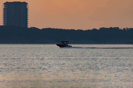 A powerboat racing across a lake just after sunrise with a tall condominium rising above the trees on the shore in the background.