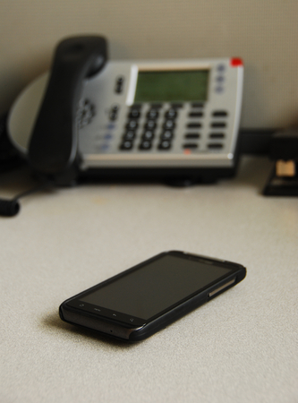 front desk: A cell phone in front of a regular phone on a desk
