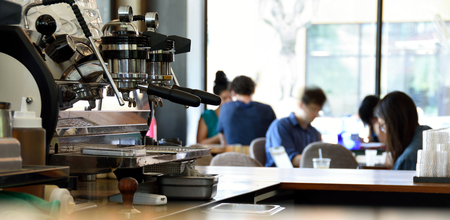An espresso machine in a busy coffee shop with unrecognizable people in the background Stock fotó