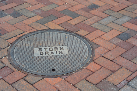 Storm Drain Cover on a Brick Road Foto de archivo