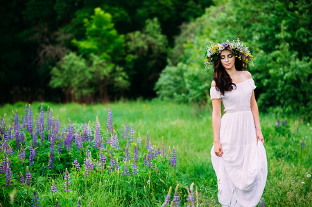 Beauty Girl Outdoors enjoying nature.Girl with a wreath of wildflowers on her head walks along the path.