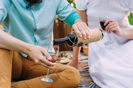 a man pouring red wine to his wine glass after he had filled hers