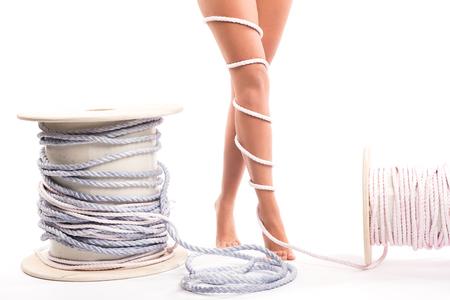 Concepto de dolor de piernas - piernas atadas con una cuerda aislada en blanco. Piernas femeninas envueltas, copyspace.