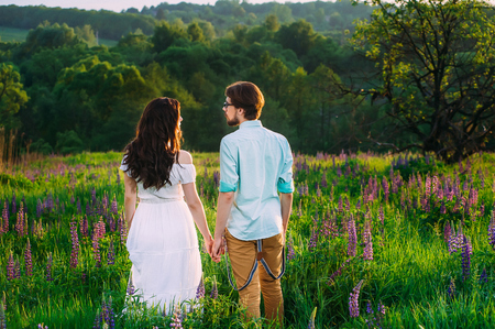 Couple in love admiring beautiful landscape together, holding hands
