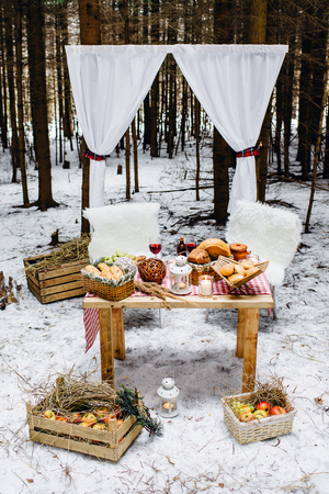 Place in winter pine wood decorated for a nice romantic picnic for two. Picnic in the winter forest Archivio Fotografico