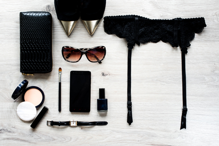 Feminine cosmetic background. Overhead of essentials of a modern woman. Top view and copy space. Sunglasses, face powder, make up brush,watch,phone,lipstick,shoes,black purse, black belt for stockings Banco de Imagens