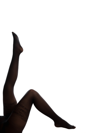 Elegant female legs in thin dark tights pointed up on a white background