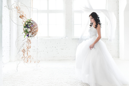 Dark haired bride in a dazzling white wedding dress in a light spare room