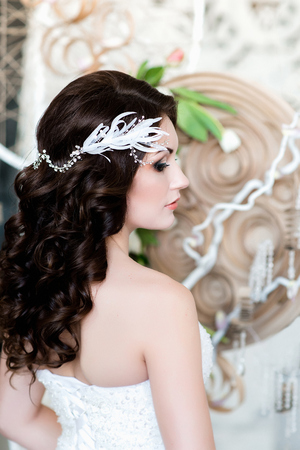Portrait of the bride.A side view of a young dark haired girl in a white wedding dress