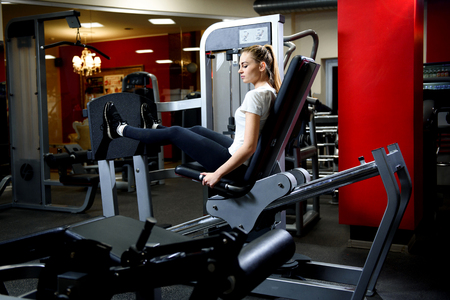 Attractive girl working our on a huge training simulator in a gym.Sportive woman using weights press machine for legs at gym.Pretty brunette exercising in simulator. Working her quads at machine. Foto de archivo