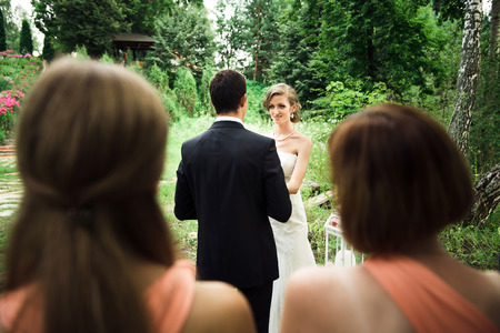 Company at the outside wedding ceremony, the newlyweds are looking at each other, trees on the background Stock Photo