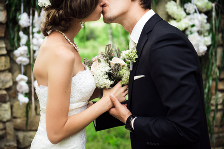 The newlyweds are kissing gently, holding hands
