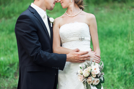 Wedding couple cuddling, nose to nose, hand in hand, isolated in green Фото со стока