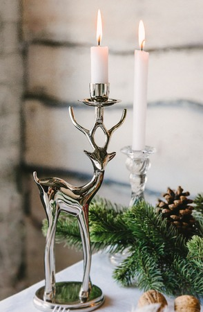 Nice candlestick designed as a deer opposite the fir branches, christmas theme