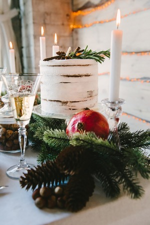Vew of fir cones, pomegranate and craft cake, burning candles behind them