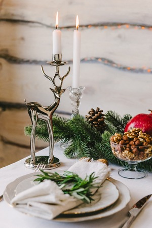 Beautiful deer candlestick with a burning candle in it, a part of a new year composition on a table