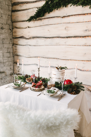 Side view of a homelike table beautifully designed in a christmas theme with fir branches, cones, pomegranate, candles and wooden walls on the background Stock fotó