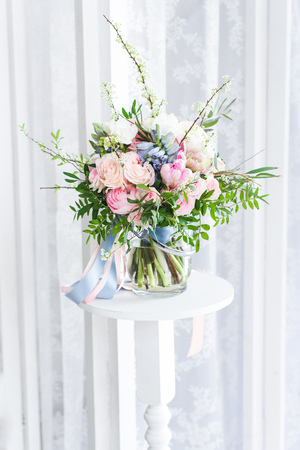 Cute bouquet of massive pink flowers with green brunches standing on a high white stand, lace white curtains behind