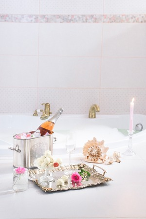 Bubble bath with champagne, red velvet cupcakes and seashell decorations, clean and pinky