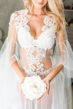 Jeune mariée dans un sous-vêtement en dentelle tenant une énorme fleur blanche, cheveux ondulés blonds sur son épaule
