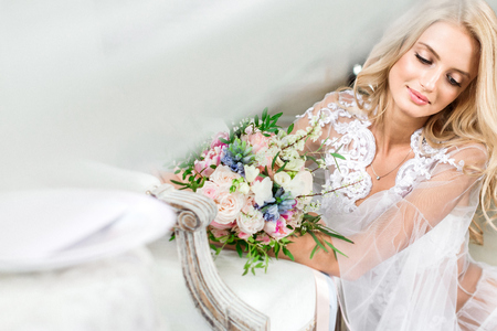 Brides morning. Fine art wedding. Portrait of a young bride in white lace boudoir with wavy blonde hair and a bouquet in her hands posing looking down shyly