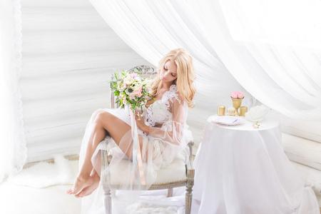 Meravigliosa sposa dai capelli biondi con biancheria intima di pizzo solo trasparente che copre il suo giovane corpo, con in mano un bouquet, in posa su una sedia, luce bianca. Mattina della sposa. Matrimonio d'arte