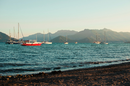 Amazing beach with blue sea, boats floating opposite the hills and a clear evening sky above