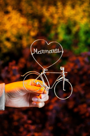Neat hand holding a wire in a shape of bicycle and heart, blurred vivid background Reklamní fotografie