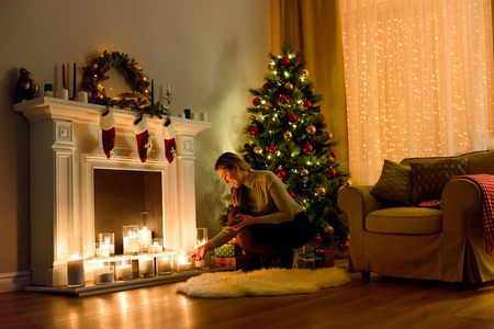 Nice woman in a cosily lighted christmas decorated room fixing candles on a fireplace.