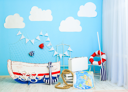 Boyish marine cute room decorated as a sea ship with a boat and fish in a web. Interior room for a boy Stock Photo