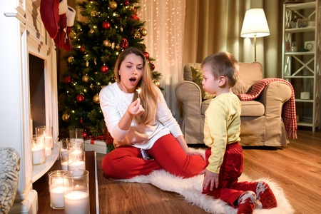 Nice young mommy blowing down a burning match, her cute little boy is helping her. Young mother and son sitting by a fireplace in a cozy dark living room on Christmas eve