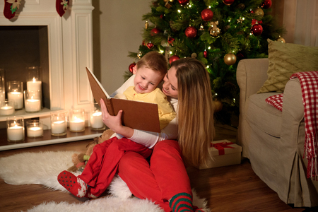 Family of a boy and his mom are reading a nice book laughing together, cozily decorated christmas room. Happy family reading together on Christmas evening.Winter evening at home for parents and kids