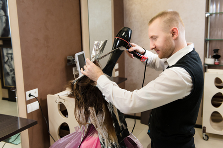 Beauty salon, hair care and people concept. A professional hairdresser dying his client's hair in a neat studio