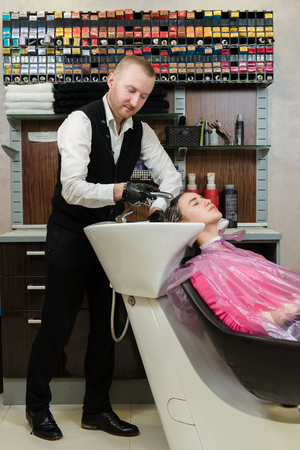 Man hairdresser washing head client the shampoo off a clients head, a rainbow of hair dying tubes on the background shelf