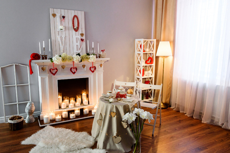 Interior for the celebration of St. Valentine's Day. A perspective photo of a cozy room with St. Valentines Day red and white decorations with a romantic table for the two