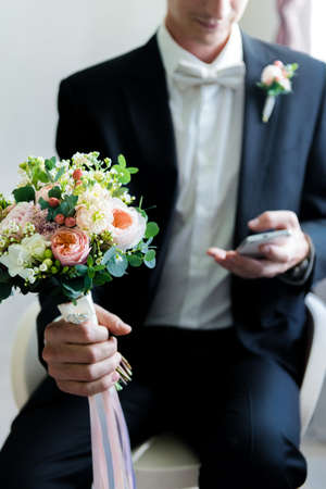 Groom with the phone. Groom in his finest look with a cute wedding bouquete types messages on his smartphone.