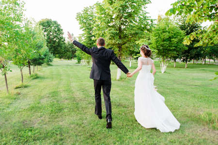 Just married couple running away happily waving their hands in a green summer garden. Just married loving couple in wedding dress and suit on green field in a forest at sunset