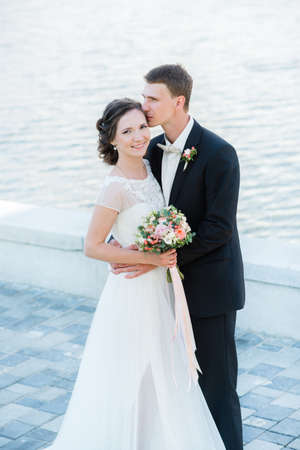 Happy young couple just married. ? lassic wedding picture of a bride and groom's huggs near the water