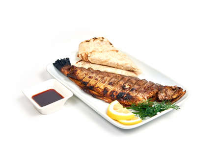 Grilled trout with vegetables on a plate isolated on white. Serving dishes in a cafe, restaurant, for a menu. Zdjęcie Seryjne