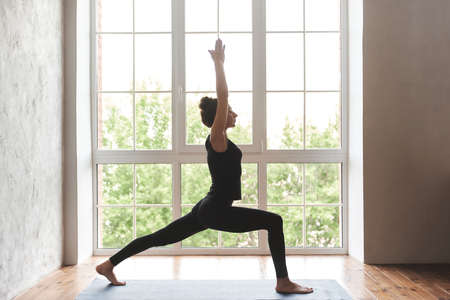 Middle aged woman practicing yoga, standing in Warrior one exercise, Virabhadrasana I pose, wearing black sportswear, at home or yoga studio with big window. Motivation healthy life concept, full length Foto de archivo