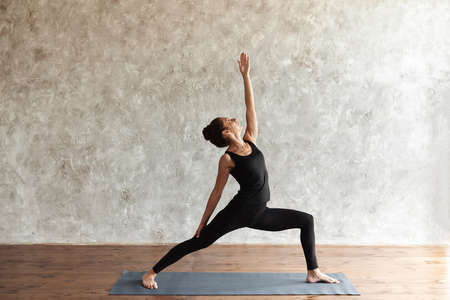 A middle-aged woman practicing yoga, looking up, standing in Reverse Warrior pose, Virabhadrasana exercise, wearing black sportswear. Home yoga sessions and healthy life concept. Advertising space