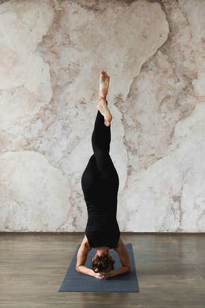 Strong woman working out indoors, doing yoga exercise, variation of supported headstand, garuda salamba sirsasana with crossed legs, wearing black sportswear, back view, full length. Foto de archivo