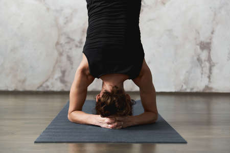 Close up of strong woman working out indoors, doing yoga exercise, variation of supported headstand. Disclosure of energy channels and home yoga sessions concept. Advertising space