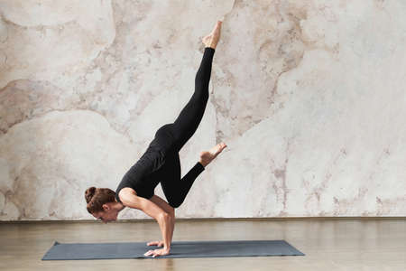 Strong woman doing Vrischikasana, Scorpion exercise, Variation of handstand pose, Pincha Mayurasana, working out, wearing black sportswear, indoor full length. Healthy life concept. Advertising space